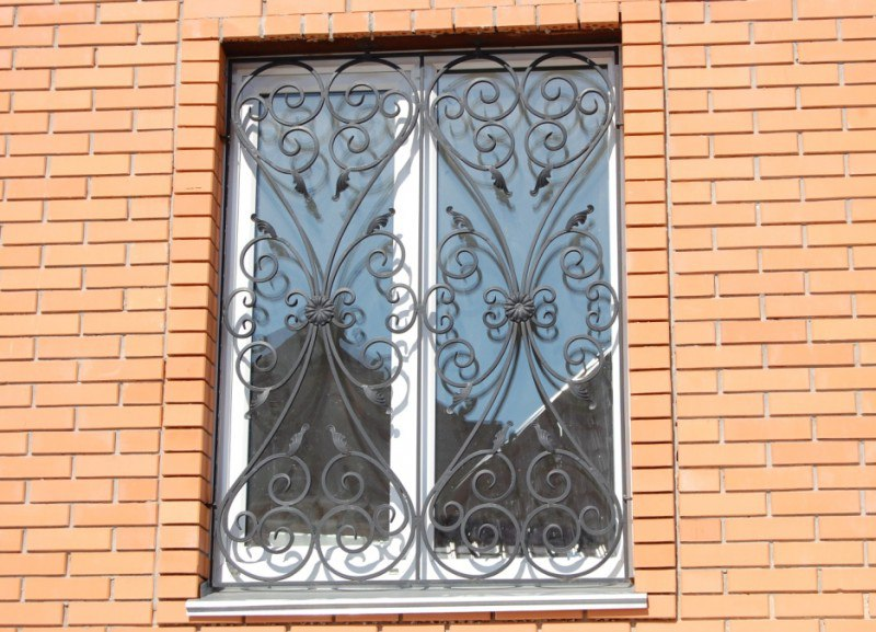 На окне кованная решётка с узорами